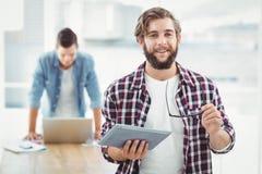 Portrait of smiling businessman holding eyeglasses and digital tablet stock images