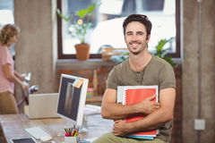 Portrait of smiling businessman holding files and folders in creative office Stock Photography