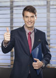 Portrait of a smiling businessman with notepad or organizer in the office showing thumb up Stock Photography