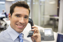Portrait of smiling businessman at phone in office, looking came Royalty Free Stock Photo