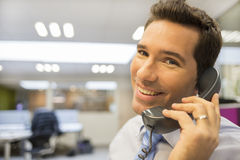 Portrait of smiling businessman at phone in office, looking came Royalty Free Stock Images
