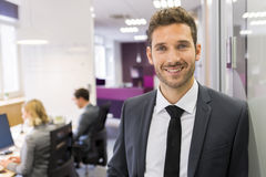 Portrait of smiling Businessman posing  in modern office, lookin Royalty Free Stock Image