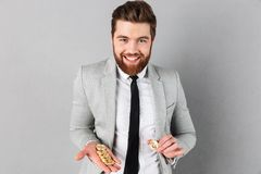 Portrait of a smiling businessman showing golden bitcoins Royalty Free Stock Photography