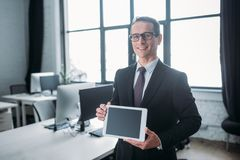 Portrait of smiling businessman showing tablet with blank screen in hands. In office stock images