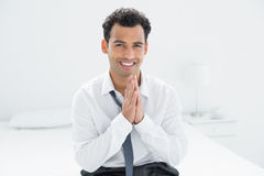 Portrait of a smiling businessman sitting on bed Stock Images
