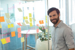 Portrait of smiling businessman standing by adhesive notes on glass Royalty Free Stock Photos