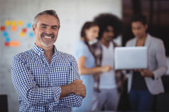 Portrait of smiling businessman standing with team in background. At creative office Stock Images