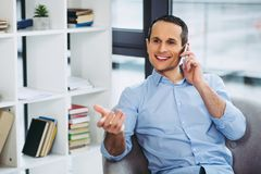 Usinessman talking on the cellphone. Portrait of smiling businessman talking on the cellphone while sitting in the armchair Royalty Free Stock Photos