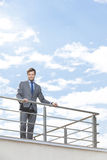 Portrait of smiling businessman at terrace railings against sky Royalty Free Stock Images