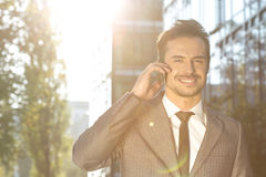 Portrait of smiling businessman using cell phone outdoors Stock Photo