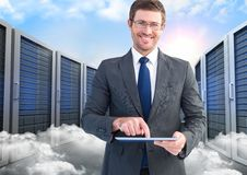 Portrait of smiling businessman using digital tablet against server and clouds background Stock Photos
