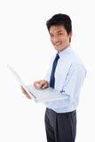 Portrait of a smiling businessman using a laptop Stock Photo