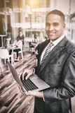 Portrait of smiling businessman using laptop. While standing in office Stock Photography