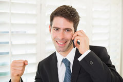 Portrait of smiling businessman using mobile phone while clenching fist Stock Images