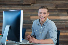 Portrait of smiling businessman working at desk. In office Royalty Free Stock Photography
