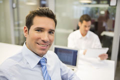 Portrait of smiling businessman working in office, looking camer Stock Photos