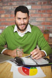 Portrait of smiling businessman writing in diary. At creative office Stock Image
