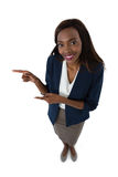 Portrait of smiling businesswoman gesturing while giving presentation Royalty Free Stock Image