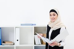 portrait of smiling businesswoman in hijab with folder royalty free stock photo