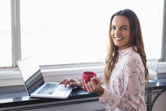 Portrait of smiling businesswoman holding coffee cup while working on laptop. By window at creative office Stock Images