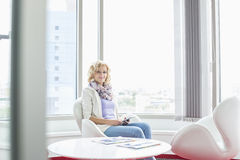 Portrait of smiling businesswoman sitting at creative office lobby Royalty Free Stock Photo