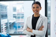 Portrait of smiling businesswoman standing with arms crossed Stock Images