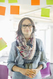 Portrait of smiling businesswoman standing by glass wall with sticky notes in office Stock Photos