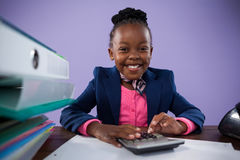 Portrait of smiling businesswoman using calculator at desk. Portrait of smiling businesswoman using calculator while sitting at desk against purple wall in Royalty Free Stock Images