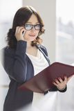 Portrait of smiling businesswoman using cell phone while holding file in office Royalty Free Stock Images