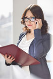 Portrait of smiling businesswoman using cell phone while holding file in office Stock Photography