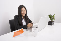 Portrait of smiling businesswoman using cell phone at office desk Stock Image