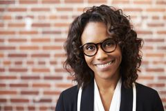 Portrait Of Smiling Businesswoman Wearing Glasses Standing Against Brick Wall In Modern Office royalty free stock photography