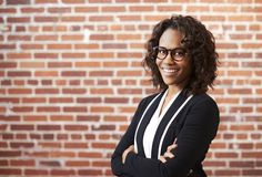Portrait Of Smiling Businesswoman Wearing Glasses Standing Against Brick Wall In Modern Office royalty free stock image