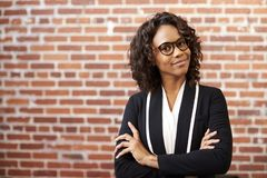 Portrait Of Smiling Businesswoman Wearing Glasses Standing Against Brick Wall In Modern Office stock images