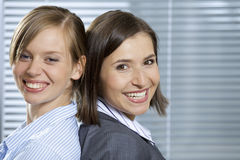 Portrait of smiling businesswomen standing back to back in office Stock Image