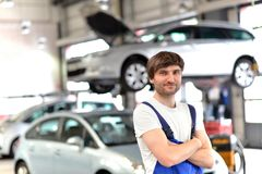 Portrait smiling car mechanic in a workshop - closeup with in th. E background car on a lifting platform Royalty Free Stock Photography