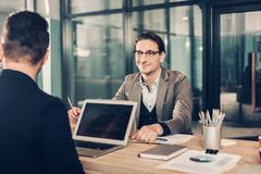 Cheerful man speaking with partner. Portrait of smiling career male telling with colleague while situating at desk in room. Comrade working with digital device Royalty Free Stock Photography