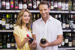 Portrait of a smiling casual couple looking at wine bottle Royalty Free Stock Photos