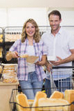 Portrait of a smiling casual couple taking a bread Royalty Free Stock Photos