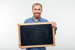 Portrait of a smiling casual man holding blank board Royalty Free Stock Photos