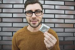 Male youngster with appealing look, holds condom royalty free stock images