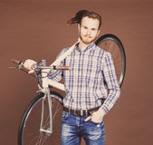 Portrait of a smiling casual man holding fixgear bicycle on the shoulder over  brown background. Toned colour Royalty Free Stock Images