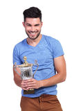 Portrait of a smiling casual man holding a trophy Stock Photo