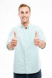 Portrait of a smiling casual man showing two thumbs up Stock Image