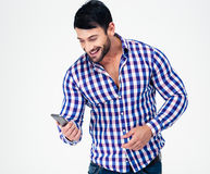 Portrait of a smiling casual man using smartphone Royalty Free Stock Photography