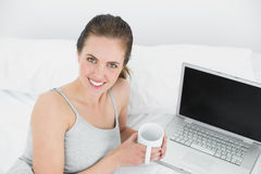 Portrait of a smiling casual woman with laptop and coffee cup in bed. Portrait of a smiling casual young woman with laptop and coffee cup in bed at home Royalty Free Stock Image