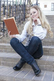 Portrait of Smiling Caucasian Blond Female With Book Sitting Straight on Stairs Outdoors and Reading Royalty Free Stock Photography