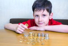 Boy with coins. Portrait of a smiling caucasian boy holding a Kazakhstani tenge coin and looking at camera. A pile of other coins is on the table surface Stock Photo