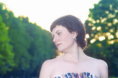 Portrait of Smiling Caucasian Brunette Woman Posing Outdoors at Sunset Royalty Free Stock Photo