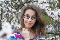 Portrait of smiling caucasian brunette woman in spring blossom garden Stock Photos